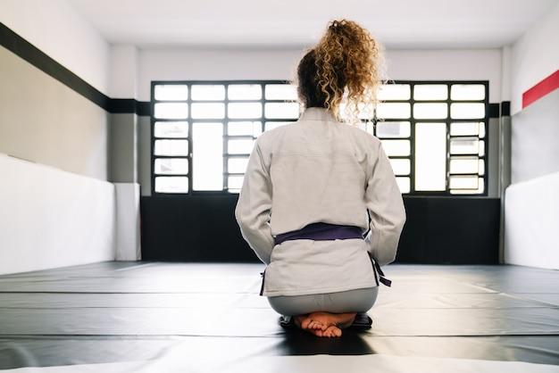 Garota deitada de costas ajoelhada no chão de uma academia praticando artes marciais como o judô