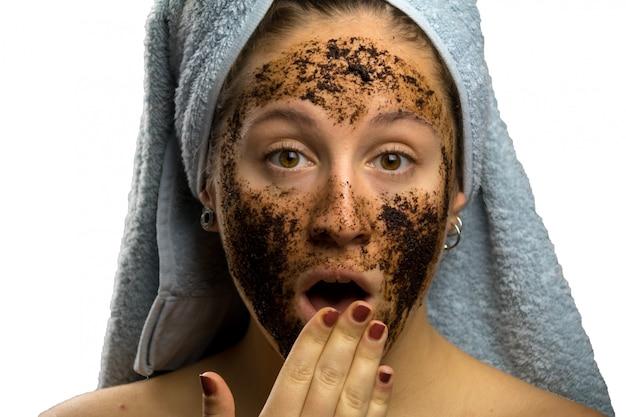 Garota depois do banho com uma toalha e diferentes expressões faciais, rosto com creme de café caseiro