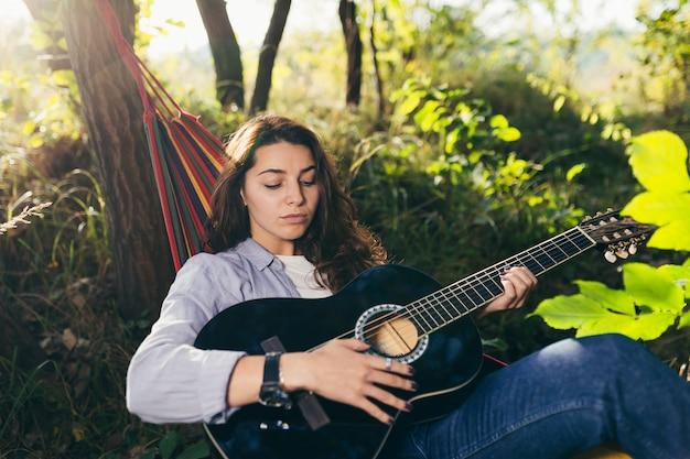 Garota descansando em uma rede com um violão no parque
