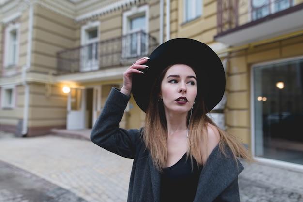 Garota descolada posa uma câmera em torno da bela arquitetura antiga.