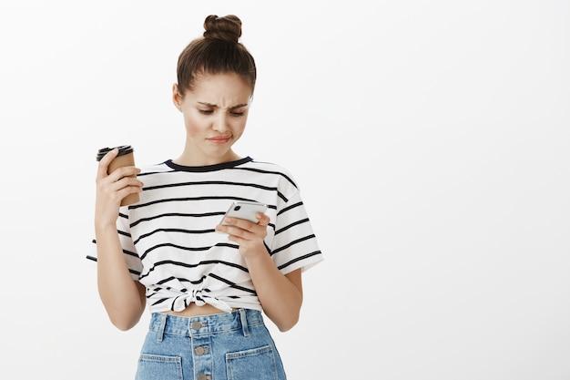 Garota descontente fazendo compras online em um aplicativo para celular, rolando perfis de aplicativos de namoro e sorrindo de decepção enquanto bebia café