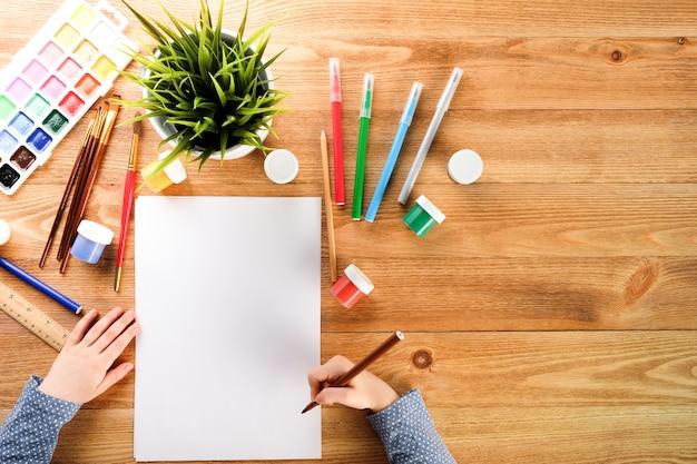 Garota desenha em um caderno com tintas e canetas de feltro. criança desenha à mesa.
