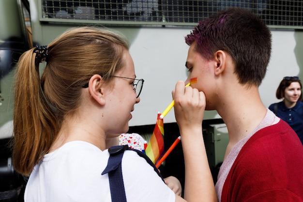 Garota desenha uma bandeira lgbt na bochecha de um jovem durante uma parada do orgulho em kiev