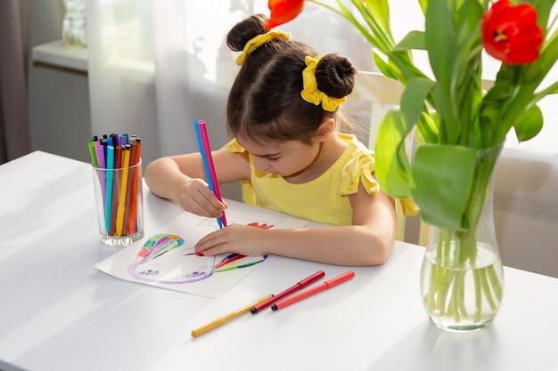 Garota desenhando com marcadores coloridos na mesa branca