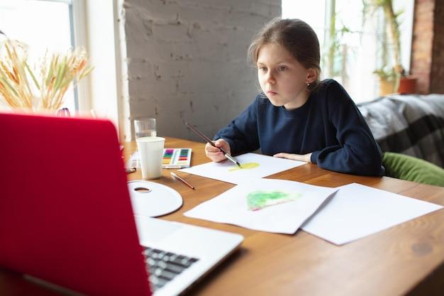 Garota desenhando com tintas e lápis em casa, assistindo o tutorial online do professor no laptop. digitalização, conceito de educação remota. tecnologias, dispositivos. homem mostrando, dando aula online. obra de arte.