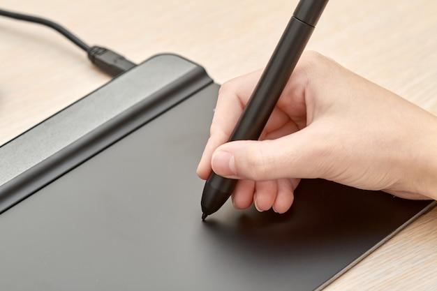 Garota desenhando em uma mesa digitalizadora com caneta
