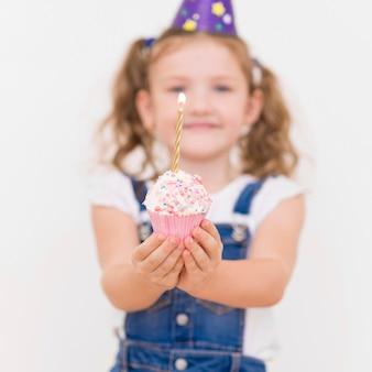 Garota desfocada com tiro médio segurando cupcake