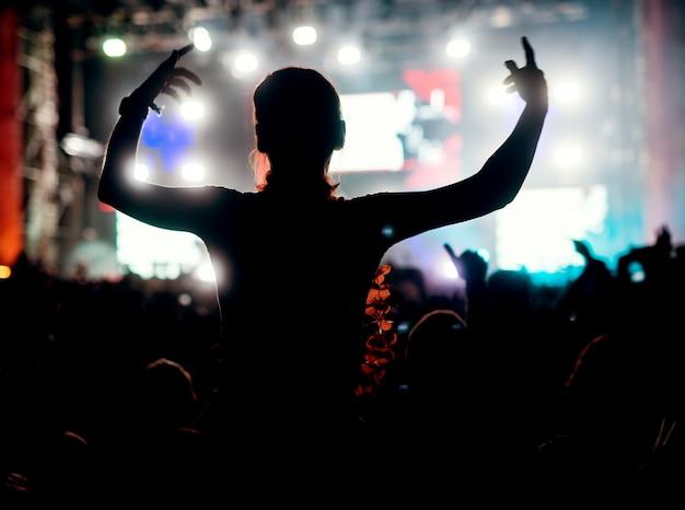 Garota desfrutando em seu festival de música multidão multidão de pessoas favoritas.