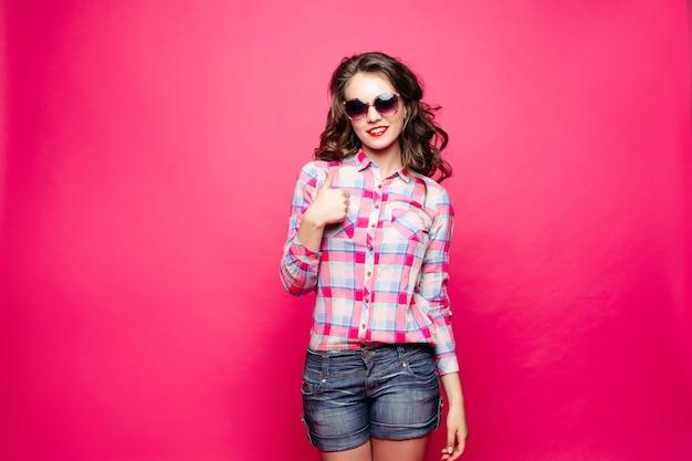 Garota deslumbrante de bermuda e camisa de óculos mostrando o sinal de paz.