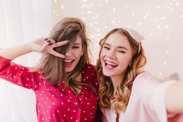 Garota deslumbrante em traje de noite vermelho, posando com o símbolo da paz, perto da irmã. adorável senhora encaracolada em máscara fazendo selfie com sua amiga.