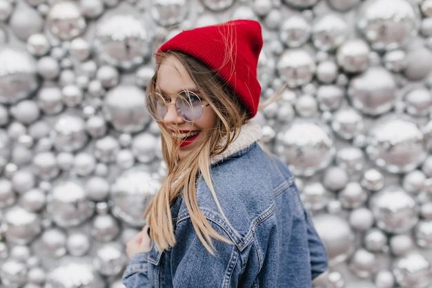 Garota deslumbrante rindo em jaqueta jeans, expressando felicidade. foto de adorável senhora de óculos posando ao lado de bolas de discoteca brilhantes e olhando por cima do ombro.