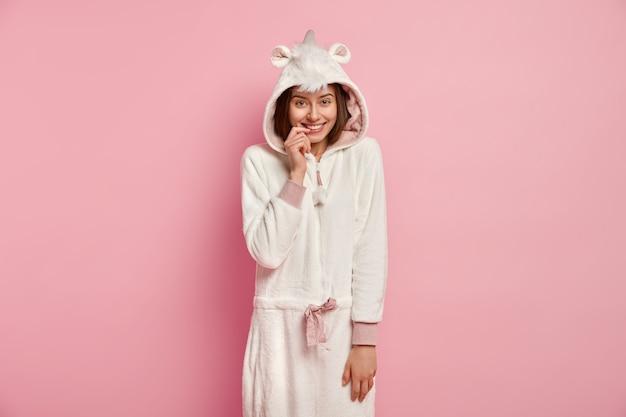 Garota despreocupada com aparência europeia, usa traje branco macio de kigurumi, mantém o dedo da frente nos lábios, encosta na parede rosa, tem tempo livre em casa. pessoas, emoções, conceito de estilo de vida