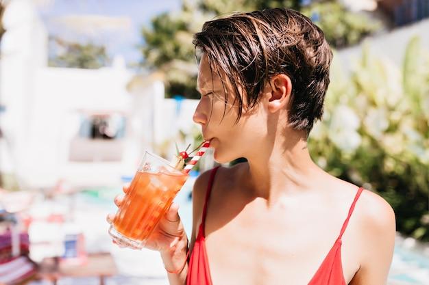 Garota despreocupada com o corte de cabelo da moda, bebendo coquetel de frutas no resort.