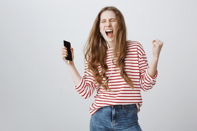 Garota despreocupada dançando e cantando com fones de ouvido, curtindo música