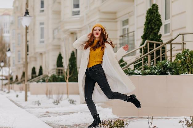 Garota despreocupada engraçada dançando em dia de inverno. foto ao ar livre da encantadora senhora ruiva com jaleco branco.