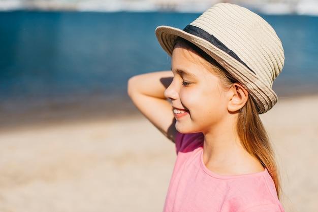 Garota despreocupada no chapéu, aproveitando o verão