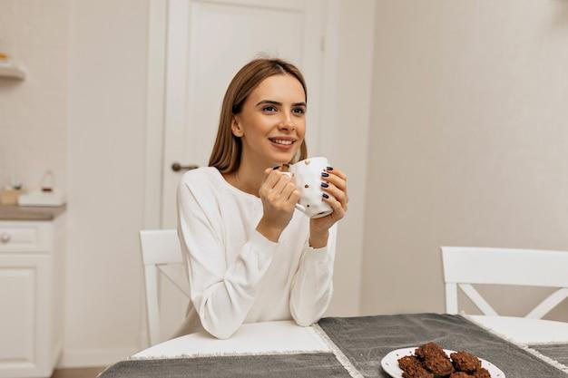 Garota despreocupada tomando café na cozinha. foto de uma mulher sorridente agradável na camisa branca, desfrutando da pausa para o café.