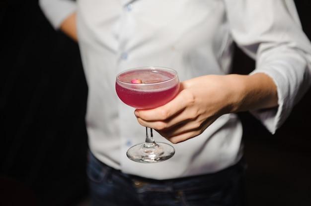 Garota detém coquetel alcoólico de cor rosa com um botão de rosa