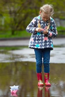 Garota dirige o barco de papel rosa em uma poça na chuva, primavera