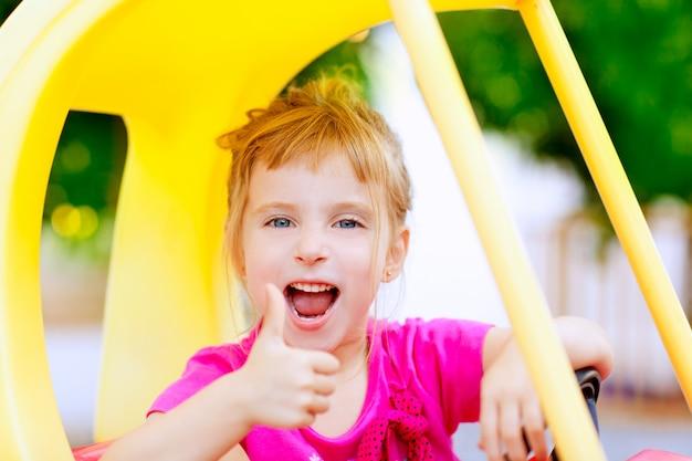 Garota dirigindo o carro de brinquedo com gesto de mão ok