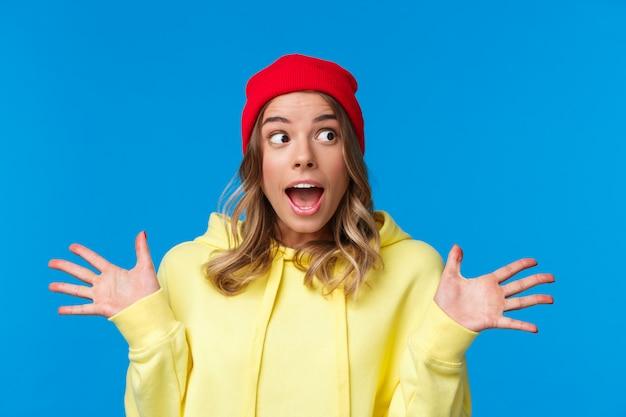 Garota discutindo notícias impressionantes, as últimas fofocas da faculdade, espalhar as mãos para o lado divertido, desviar o olhar ofegante, tendo uma conversa interessante, usar gorro vermelho e capuz amarelo