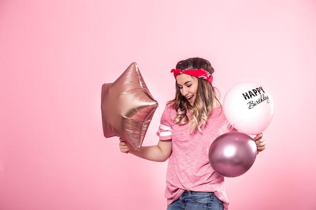 Garota divertida em uma camiseta rosa com balões feliz aniversário sorri e emociona