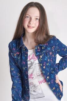 Garota divertida moda em jeans posando em um fundo branco. escola modelo para crianças.