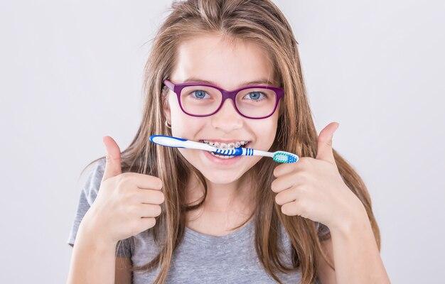 Garota do aparelho dentário com escova de dentes, fazendo o polegar para cima gesto de sinal com a mão. conceito de ortodontista e dentista.