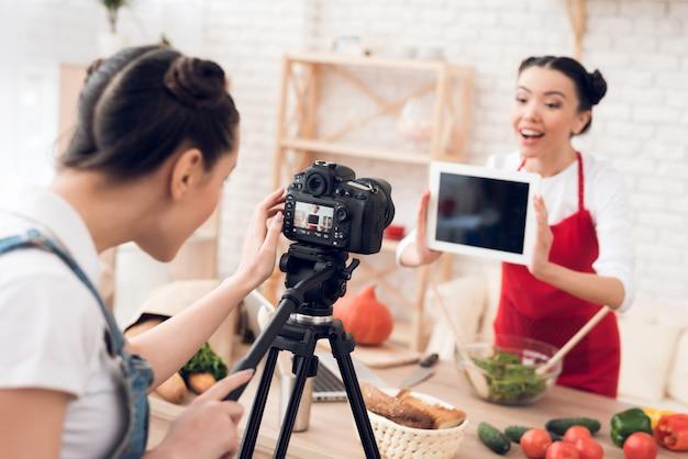 Garota do blogger sustenta o tablet em branco para a câmera.