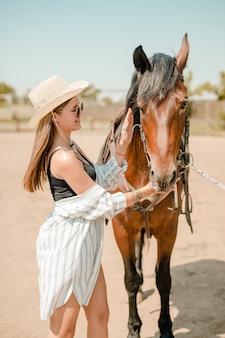 Garota do campo em um rancho com um cavalo castanho