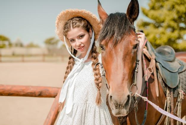 Garota do campo no chapéu de cowboy com um cavalo em uma fazenda