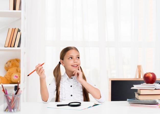 Garota do ensino fundamental pensando em resposta na tarefa