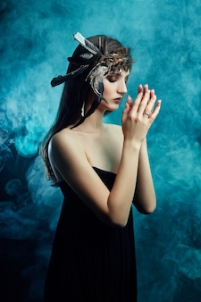 Garota do índio americano com penas no cabelo e maquiagem no rosto em fumaça azul no preto