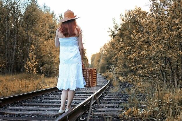 Garota do parque outono com um vestido de verão branco e uma mala de vime andando sobre os trilhos