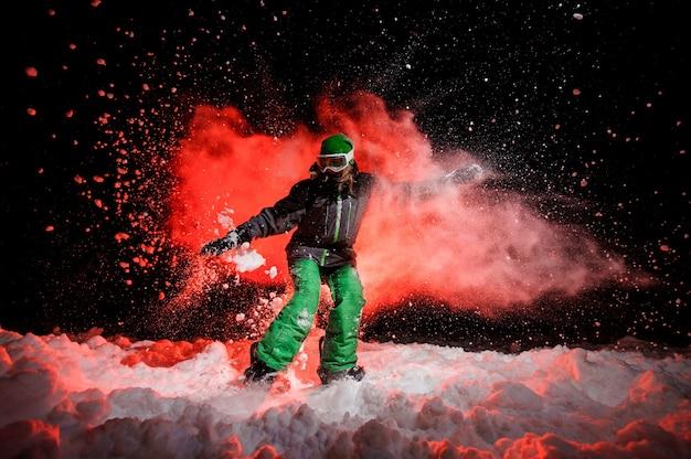 Garota do snowboarder vestida com uma roupa esportiva verde em pé na colina da montanha à noite sob a luz vermelha