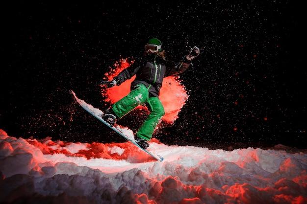 Garota do snowboarder vestida com uma roupa esportiva verde, pulando na colina da montanha à noite