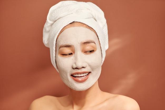 Garota do spa com expressão facial satisfeita, aplica máscara de argila no rosto, faz tratamentos de beleza, usa toalha branca macia na cabeça