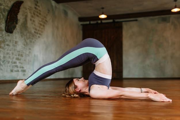 Garota do yoga realiza um exercício difícil no loft