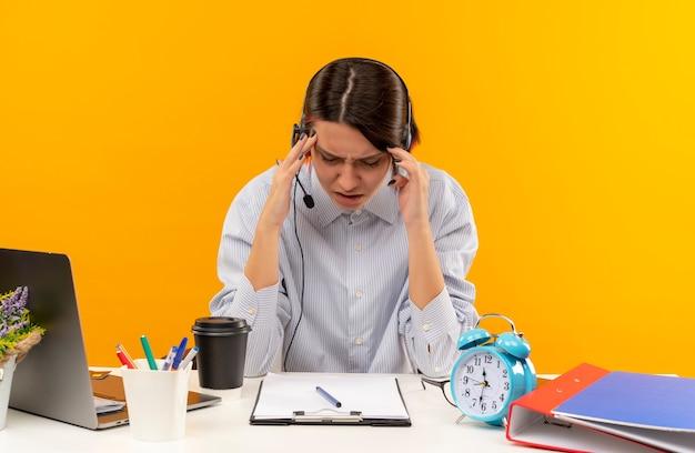 Garota dolorida do call center usando fone de ouvido, sentada na mesa, colocando as mãos na cabeça, sofrendo de dor de cabeça com olhos fechados, isolado em laranja