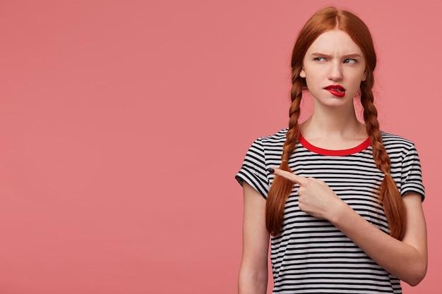 Garota duvidosa e pensativa com duas tranças ruivas mordendo lábio vermelho pensa em alguma coisa, vestida com camiseta despojada, olha para o canto superior esquerdo apontando dedo indicador isolado