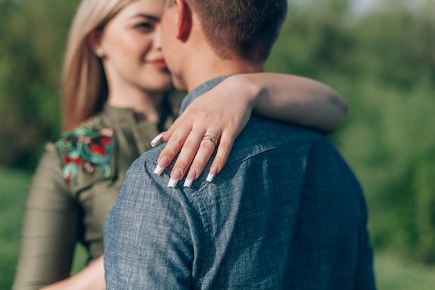 Garota e cara amorosa beijos na natureza. história de amor ao ar livre. amantes andando na primavera park.portrait emocional casal caminhando ao ar livre em dia de sol na primavera.