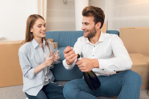 Garota e cara comemoram a mudança para o apartamento com champanhe.