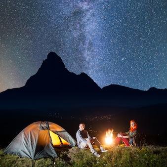 Garota e cara sentado pela fogueira sob o céu estrelado