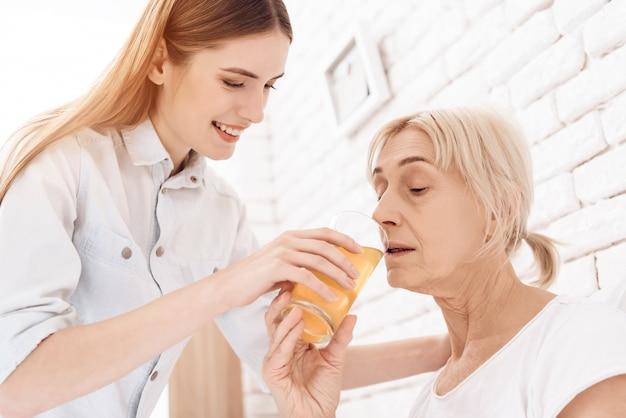 Garota é cuidar da mulher idosa na cama em casa