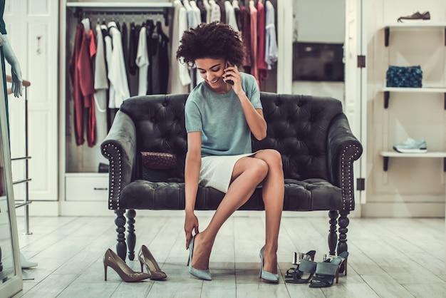 Garota é escolher sapatos de salto alto, falando no celular.