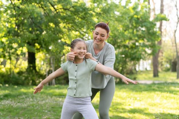 Garota e mulher em tiro médio fazendo exercícios ao ar livre