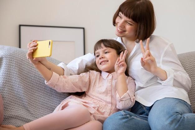 Garota e mulher em tiro médio tirando selfies