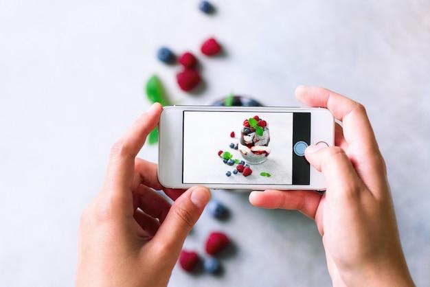 Garota é tirar fotos do café da manhã, pudim de chia com frutas para o telefone móvel.