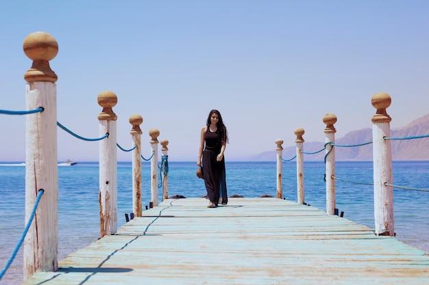 Garota egípcia caminhando em um píer de madeira na lagoa dahab