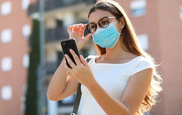 Garota elegante hipster de estilo de vida cidade com máscara cirúrgica, lendo uma mensagem no celular na rua